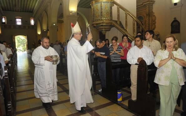 Mons. Valenzuela, con el hisopo en mano, asperja con agua bendita a los fieles. Detrás un sacerdote lleva el acetre con el vital líquido. : abc color