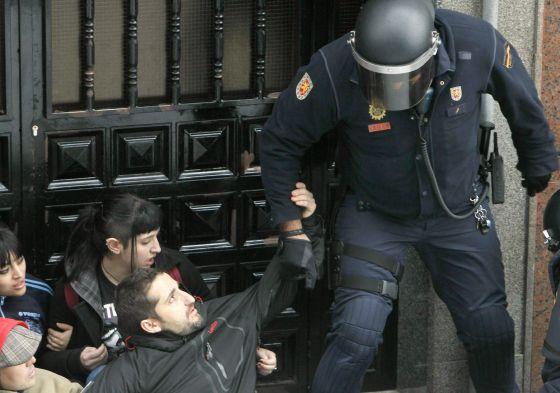 Un agente desaloja de la puerta de una vivienda de Torrejón (Madrid), a las personas concentradas para apoyar a un desahuciado.