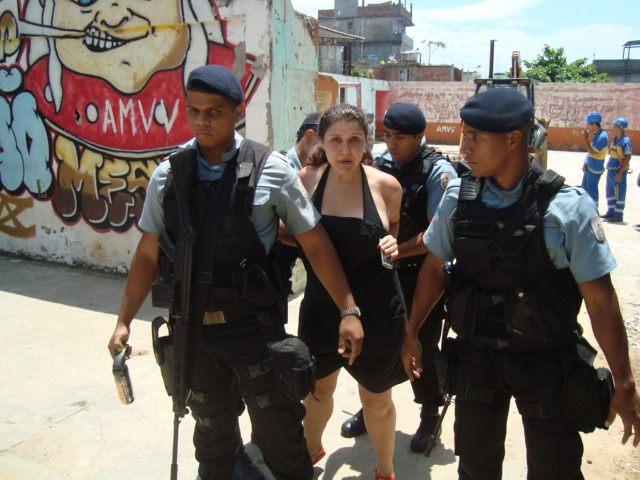 Mariana carregada presa. Um dos policiais tem a arma engatilhada