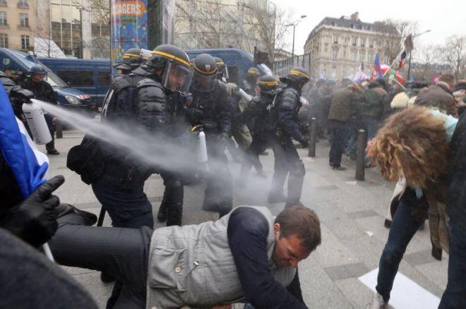 Les gendarmes mobiles ont fait usage de gaz lacrymogènes pour repousser des manifestants qui tentaient de forcer le barrage vers les Champs-Élysées. Crédits photo : THOMAS SAMSON/AFP