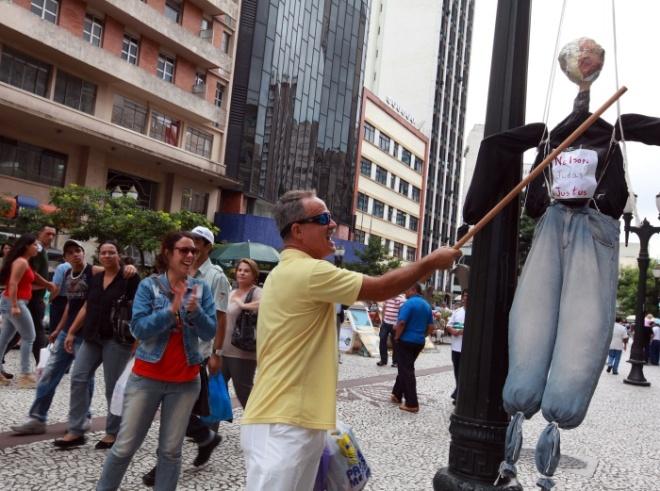 """Em Curitiba, boneco representando o presidente da Assembleia Legislativa do Paraná, Nelson Justus, foi """"malhado"""" na Boca Maldita"""