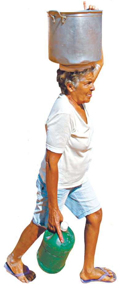 Antônia da Silva, de Canindé, equilibra-se com panela d´água na cabeça