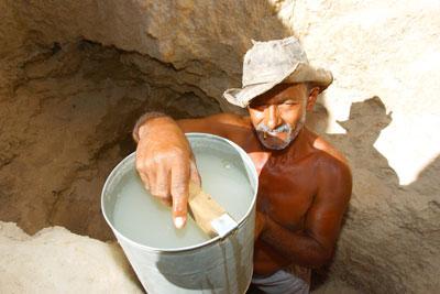 Luís Venerando Sobrinho mostra a água, de aparência leitosa. O recurso é consumido depois de coado em um pano