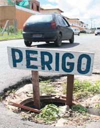 Na rua Praia do Atalaia, moradores improvisaram uma placa para alertar os motoristas para a armadilha