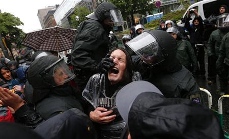 Polícia de choque entra em confronto com manifestante diante da sede do BCE durante protesto anticapitalista, em Frankfurt