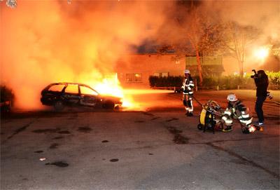 Un grupo de bomberos trata de extinguir un vehículo en llamas.- EFE