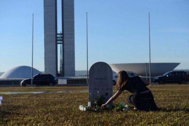 """Manifestante """"enterra"""" corrupção em frente ao Congresso Nacional em Brasília"""
