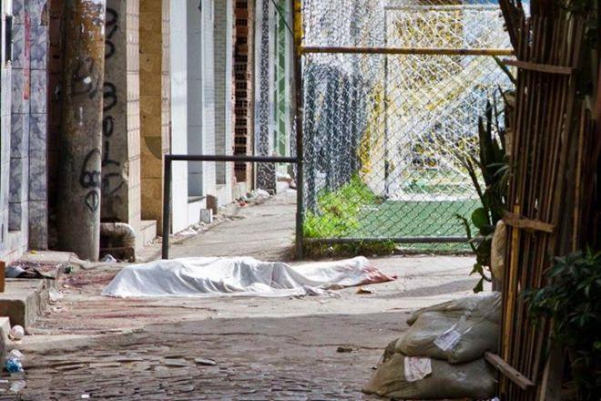 Um dos treze cadáveres abandonados nas travessas da favela