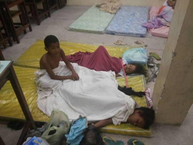 Isac Alves ainda acordado ao lado das irmãs, Maria Gabriela e Rebeca Alves, que  dormem numa das salas do Colégio Municipal dos Coelhos