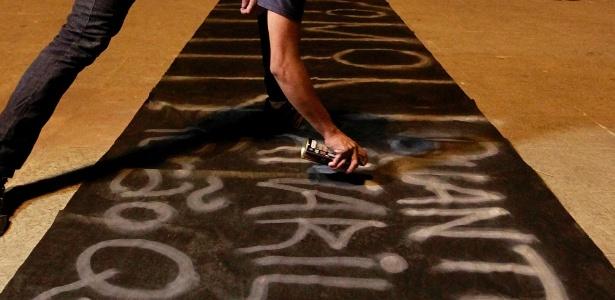 Manifestante escrevendo o nome de Amarildo em uma improvisada faixa. Amarildo representa os 200 mil brasileiros que estão sendo despejados para os governadores - os novos Neros - construírem estádios e obras complementares para a Copa de 2014