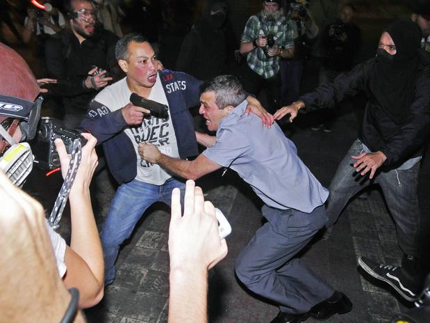 Coronel Reynaldo Simões Rossi protegido por um policial