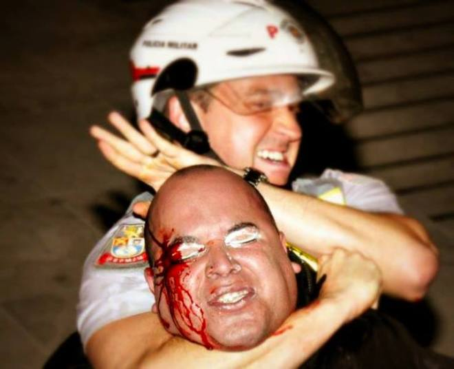 """FOTO: Eli Simioni AUDIODESCRIÇÃO: ( Policial Militar aplica um """"Mata-Leão"""" em um manifestante, a cena captura com perfeição a sensação de dor do manifestante, que está com o rosto sangrando. )"""