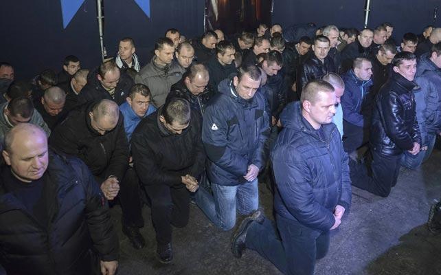 Ucrânia. Policiais antidisturbios pedem perdão de joelhos