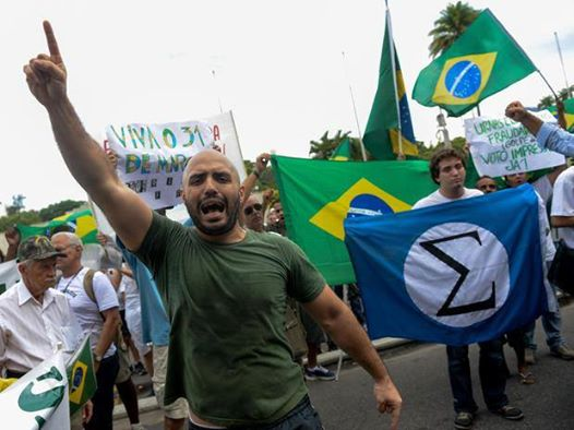 O nazismo à Plínio Salgado. Manifestante exibe bandeira do Integralismo durante Marcha da Família com deus (que deus?) pela Liberdade.