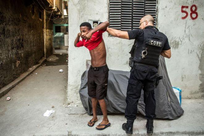 Policial do CORE (Coordenadoria de Recursos Especiais da Polícia Civil) revista morador do Complexo da Maré, no Rio de Janeiro. A ocupação faz parte do processo de instalação das Unidades de Polícia Pacificadora (UPP) no local