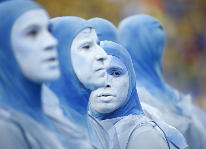 Performers dance in costumes during the 2014 World Cup opening ceremony at the Corinthians arena in Sao Paulo