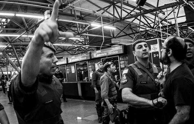 Audiodescrição dos Fotógrafos Ativistas: Dois policiais militares e um manifestante. Um dos PMs empurra o manifestante para trás enquanto o outro em primeiro plano, aponta o caminho que devem seguir em tons autoritários