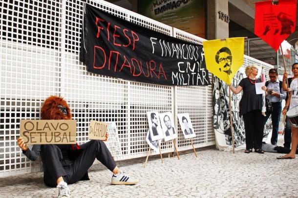 """Usando uma máscara de gorila, uma atriz segurava cartolinas com os nomes """"Dr Geraldo"""" e """"Olavo Setúbal"""", em referência a Geraldo Resende de Mattos, ex-funcionário da Fiesp, e ao banqueiro Olavo Setúbal, que foi prefeito biônico de São Paulo, entre 1975 e 1979."""