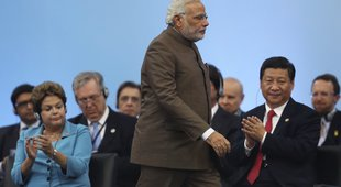 Indian PM Modi walks past Chinese President Xi Jinping and Brazilian  President Rousseff during the 6th BRICS Summit in Fortaleza