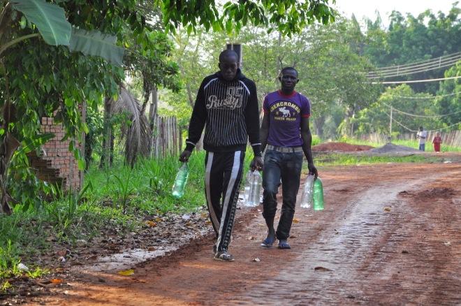 Senegaleses, às 6h10, após abastecerem garrafas com água na vizinhança do abrigo