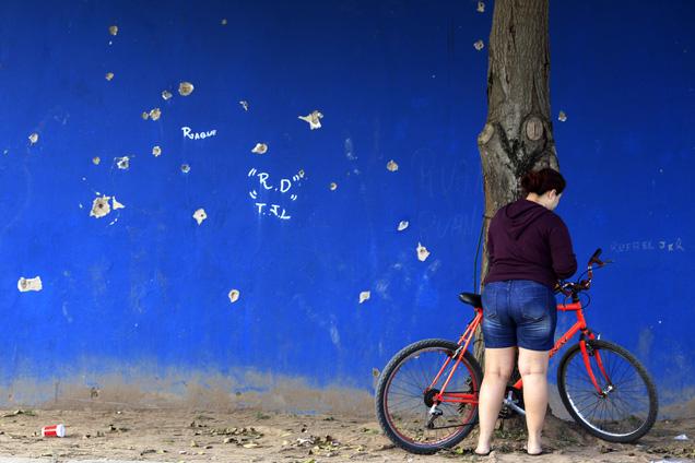 Junto a uma parede cravejada de balas, na favela da Maré, também se vê a diversidade do Brasil foto RICARDO MORAES/REUTERS