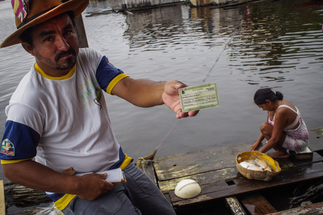 O pescador António Lopes da Silva, mostra o cartão de eleitor enquanto a mulher, Patrícia Helena Batista, amanha o peixe para o almoço, numa casa flutuante em Iranduba foto RAPHAEL ALVES/AFP
