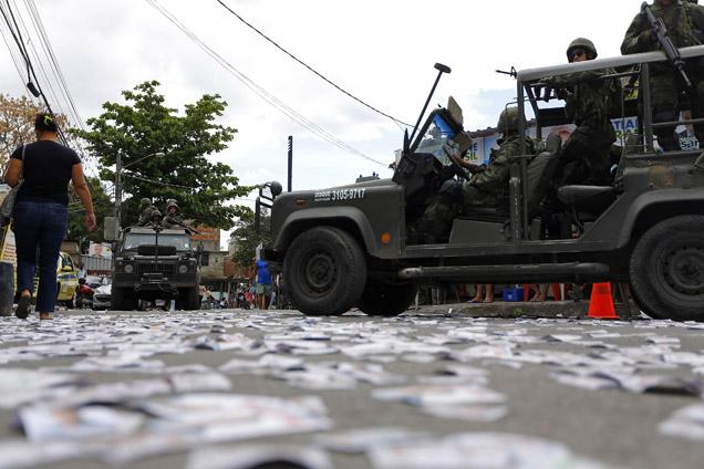 Fuzileiros da marinha brasileira patrulham ruas da favela da Maré, repletas de boletins de voto foto RICARDO MORAES/REUTERS