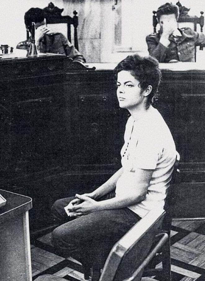 """Dilma Rousseff é interrogada por militares em 1970, logo após sua prisão. """"Acho que nenhum de nós consegue explicar a sequela. A gente sempre vai ser diferente"""", relatou depois de eleita presidenta. """"As marcas da tortura sou eu. Fazem parte de mim"""". Envergonhados, os oficiais da justiça militar, tapam os rostos. Até hoje, eles não têm nenhum orgulho da ditadura."""