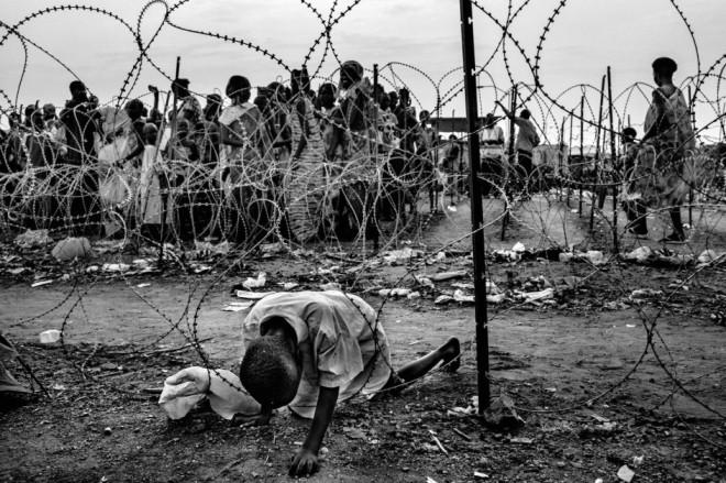 ON THE BRINK OF AN ABYSS - FABIO BUCCIARELLIUn niño de la etnia Nuer intenta cruzar una alambrada en el campo de refugiados de Juba.  Foto de Fabio Bucciarelli, finalista del premio de FotoEvidence con un reportaje sobre la situación en Sudán del Sur (© Fabio Bucciarelli - Courtesu FotoEvidence) Ver más en: http://www.20minutos.es/fotos/artes/premio-fotoevidence-2015-11201/?imagen=1#xtor=AD-15&xts=467263