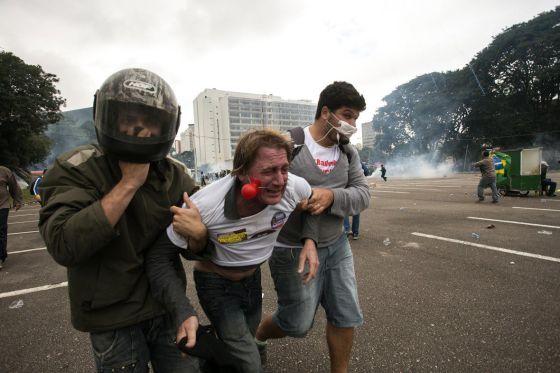 Manifestante afetado por gás lacrimogêneo é atendido. / LEONARDO SALOMAO (AFP)