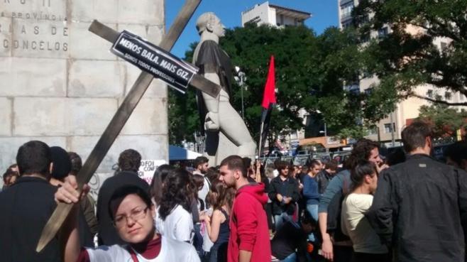 """Manifestante mostra cruz com a frase: """"Menos bala, mais giz"""" (Crédito: Antonio More/Gazeta do Povo)"""