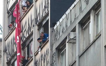 Moradores observam policiais convocados para retirar ocupantes de prédio no centro de São Paulo. Foto ZANONE FRAISSAT/FOLHAPRESS